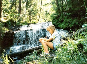 Child reading by waterfall. Image by Julie Falk.